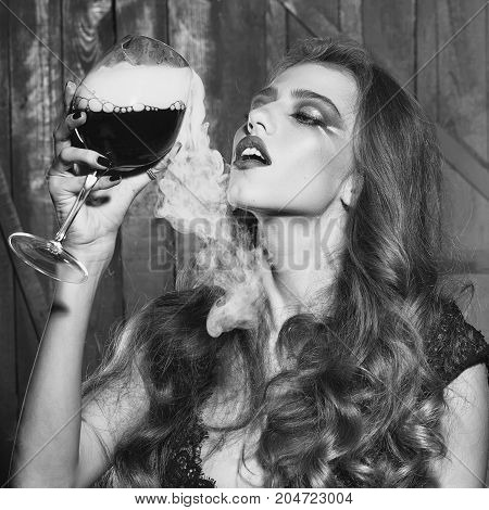 One beautiful enigmatic sexy young fashionable sensual girl with long curly hair bright makeup in black cloth holding glass goblet with red wine with smoke on wooden background square picture