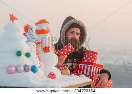 Man With Present Boxes On Snowy Landscape