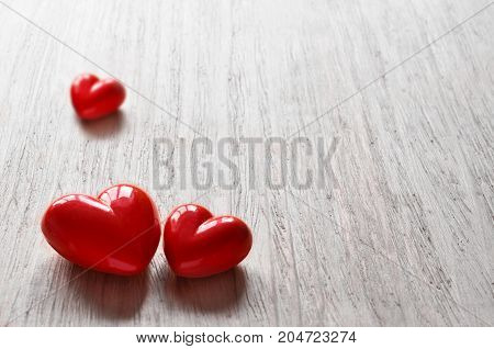 Three candy hearts for Valentine's Day with grey background.
