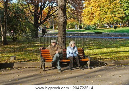 Moscow Russia - October 12 2013: Elderly couple sitting on bench in autumn park Gorkogo in Moscow