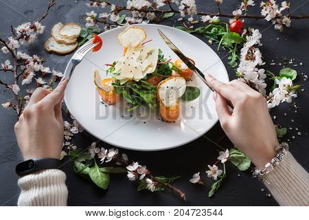 Female eating restaurant dish with fork and knife on white plate on gray background decorated with flowers, greens and tomatoes. Salad with spinach, arugula, cheese, salmon and baguette, top view