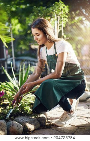 Young girl gardening digging soil on her mid term vacation from high school. Summer work concept.