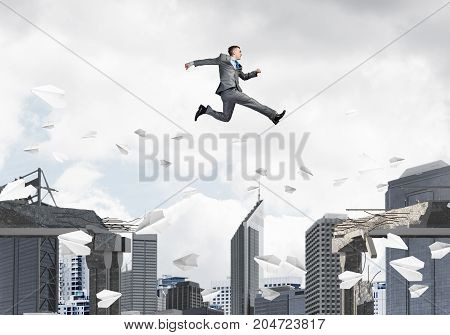 Businessman jumping over gap with flying paper planes in concrete bridge as symbol of overcoming challenges. Cityscape on background. 3D rendering.