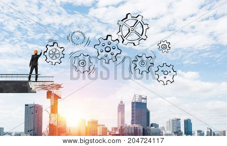 Businessman in helmet drawing sketches of gear mechanism while standing on broken bridge with cityscape and sunlight on background. 3D rendering.