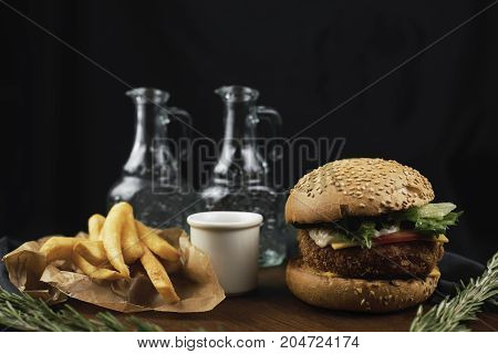 Craft beef burger and french fries on wooden table on dark blue background.