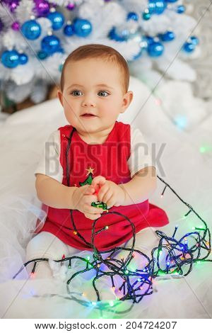 The little baby is sitting in the garland. The concept of Merry Christmas New Year family.
