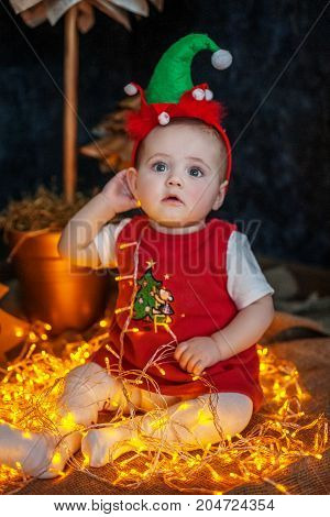 The little baby is sitting and enjoying. The concept of Merry Christmas New Year family.