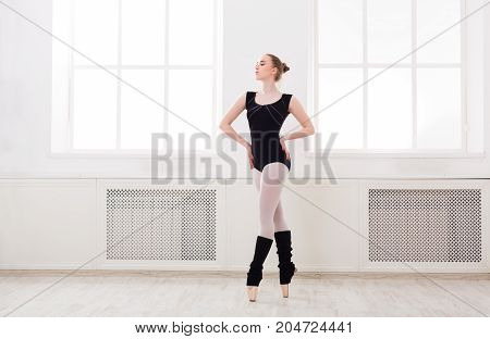 Young graceful ballerina in black at ballet class making croise. Classical dancer in white hall practicing positions near large window, copy space