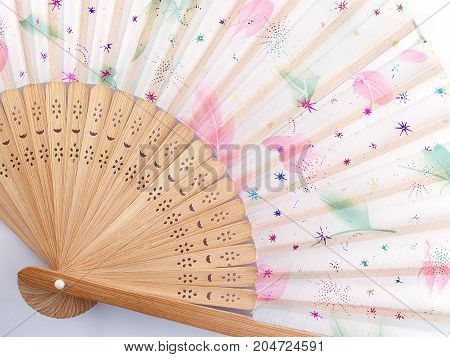 closeup folding fan Chinese or Japanese style made by bamboo and fabrics painting patterned colorful leaf, top view