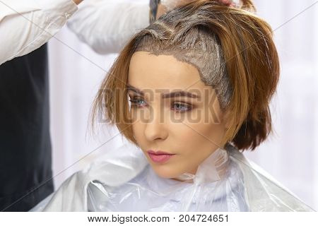 Hair dying process, beauty salon. Face of attractive young woman.
