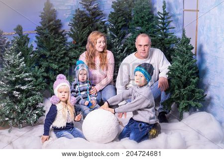 Studio shot of family, consisting of parents and three kids, playing with snow balls at winter time