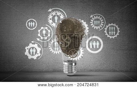 Lightbulb with multiple gears inside placed against social gear structure on grey wall. 3D rendering.