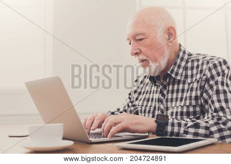 Senior man typing on laptop sitting at table at home, copy space