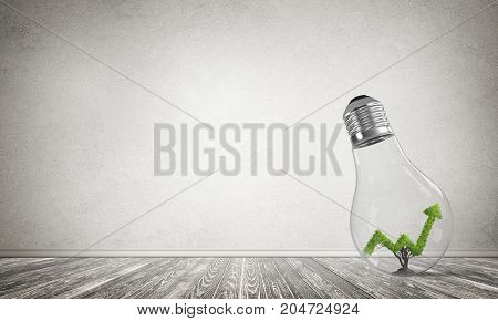 Glass lightbulb with growing green arrow graph inside in empty room with grey wall on background. 3D rendering.