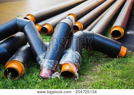 Water pipes with insulation lie on the grass. Pipe for water. Hot water supply. Serve water. Central water supply.