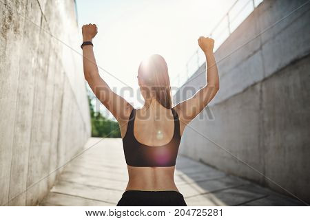 Female champion running into sun to celebrate her victory. Urban workout concept.
