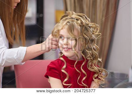 Smiling little girl, hair salon. Caucasian child at the hairdresser.