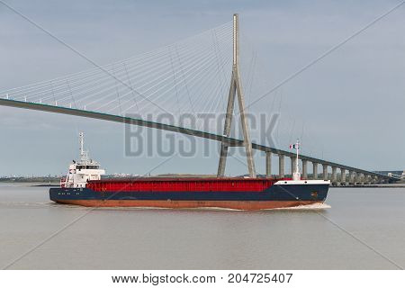Cargo ship passing Pont de Normandie over river Seine in France
