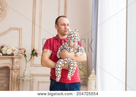 Father holding and playing his little baby child son.