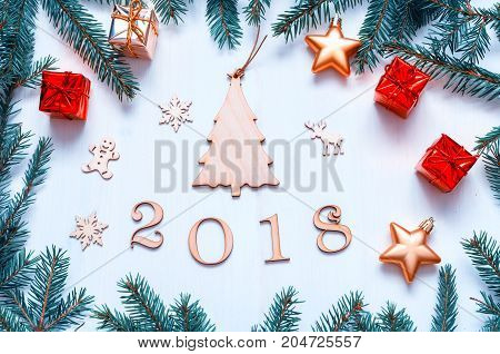 New Year 2018 background with figures Christmas toys with frame of blue fir branches. New Year 2018 composition. Flat lay top view of New Year 2018 festive still life