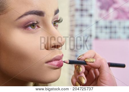 Hands using lip pencil. Makeup close up. Professional cosmetics advertising.