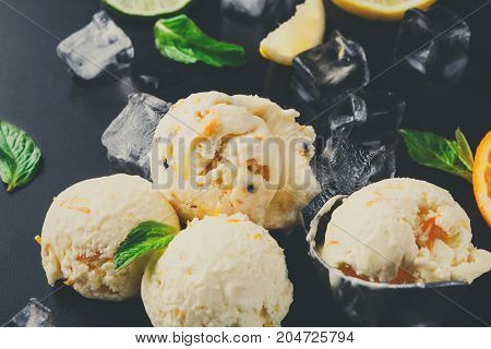 Ice cream scoops with ice cubes, lemon and orange slices, mint and scoop on black background. Delicious cold sweet dessert, close up