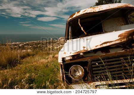 Old van abandoned in the hills of a mediterranean country, with the mediterranean sea in the background