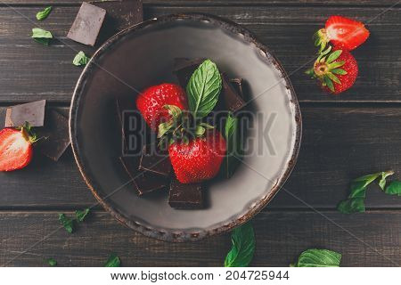 Fresh strawberries with chocolate in rustic bowl. Sweet summer dessert, homemade fondue