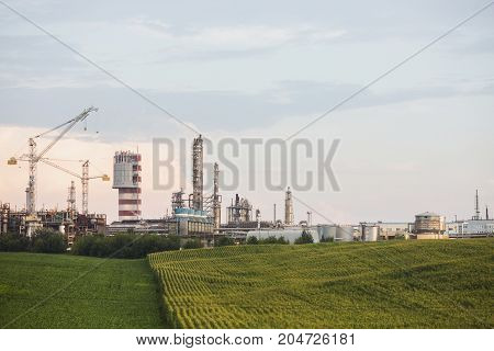 A large factory processing plant. Pollution of air and atmosphere . The factory pipes emit dirty smoke. The factory pollutes the nature. Large factory chimneys. The factory stands outside the city