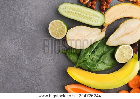 Healthy food background. Different vivid fruits and vegetables on gray table, top view, copy space. Ingredients for detox smoothie.