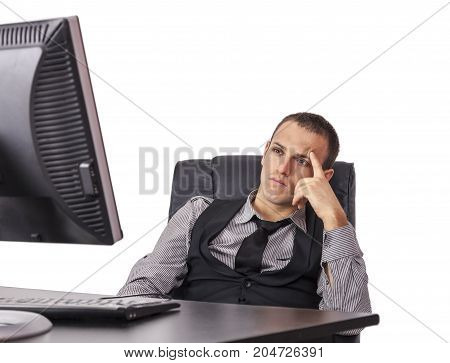 Tired young businessman sitting in front of his computer with a thinking attitude isolated against a white background.