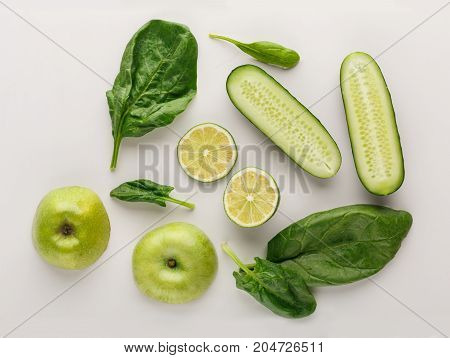 Healthy food. Ingredients for detox smoothie, lime, cucumber, spinach, apple on white background, top view, copy space.