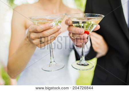 The bride and groom holding glasses with champagne Wedding ceremony. A glass of champagne. Champagne in hand. Drink champagne for the holiday. Two champagne bakery. The bride and groom with champagne
