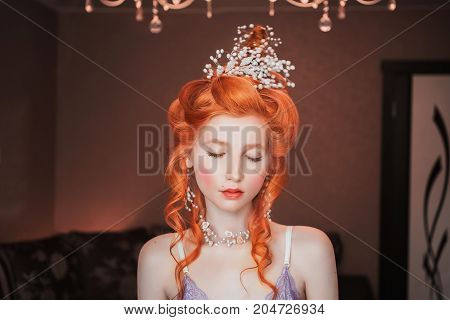 Пlamour woman with pale skin and a high glamour hairdo with beautiful precious glamour ornaments from white beads. Beautiful glamour girl with red lips. Glamour model. Glamour make up