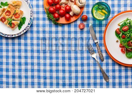 Healthy eating concept. Fresh salad with greens, tomatoes and mushrooms, casserole and lemonade on checkered tablecloth background. Organic vegetables top view, copy space.