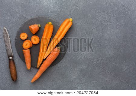 Cut carrots on rustic slate stone plate. Cooking healthy food on gray background, copy space, top view.