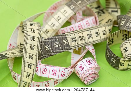 Measuring Tape Of The Tailor Isolated On Green