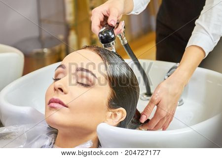 Lady getting her hair washed. Beauty salon customer, closed eyes. Top quality hair conditioner.