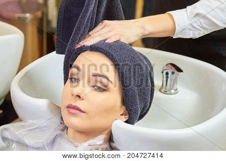 Woman at the hairdresser, towel. Hair salon customer, sink.