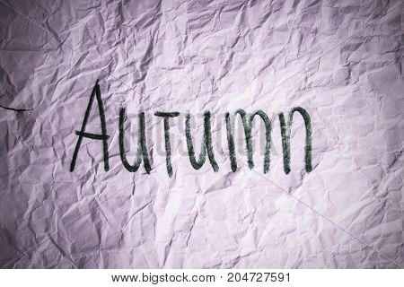 Depressive autumn word on crumpled paper texture in dark vignette