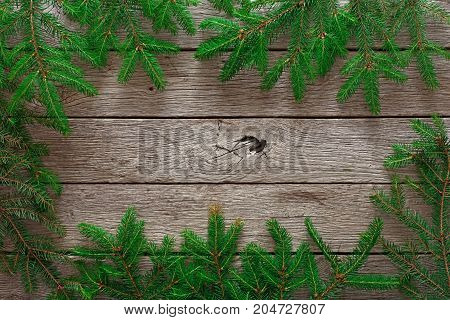 Christmas decoration, frame concept background, top view with copy space on gray rustic wood table surface. Christmas border with fir tree branches