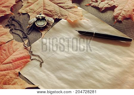 Autumn background. Old paper ink pen on the table among the autumn leaves. Focus at the ink pen.Vintage autumn still life. Autumn vintage background. Autumn still life. Vintage autumn composition