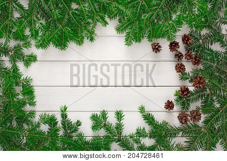 Christmas background with copy space, top view on pine tree twigs and cones frame on white rustic wood table surface. Xmas decorations, winter holidays concept