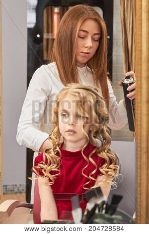 Little girl in hairdressing salon. Female stylist using hairspray. Hypoallergenic hair spray.