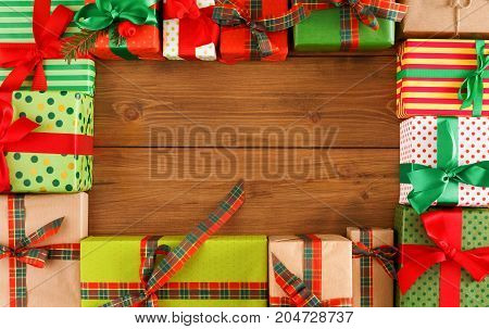 Lots of gift boxes on wood background top view. New year. Presents in craft and colored paper decorated with red and green ribbon bows. Christmas and other holidays concept.