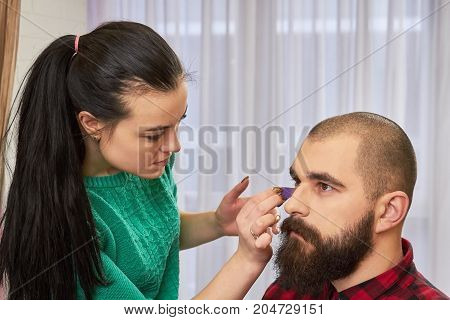 Female makeup artist applying foundation. Face of bearded young man.