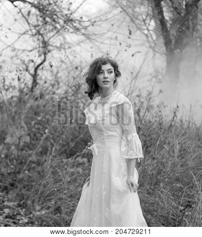 Beautiful young lady in gorgeous vintage white dress in the forest. Late autumn cold. Portrait outdoors. Black and white.