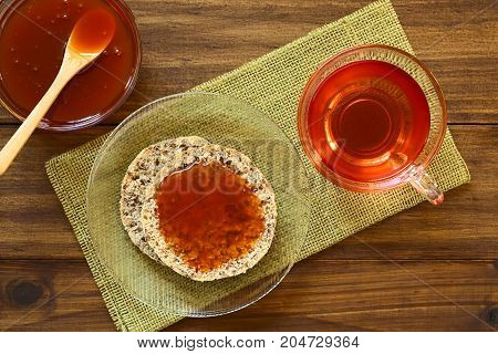 Homemade rose hip jam on wholegrain rolls with rose hip tea on the side photographed overhead on wood with natural light