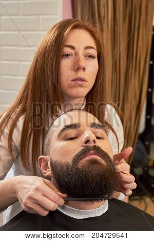 Female barber working with customer. Bearded guy in barbershop. How to become a barber.