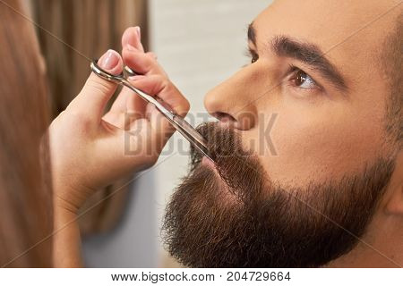 Bearded face, hand with scissors. Facial hair trimming, close up.